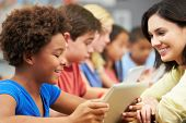 stock photo of 11 year old  - Pupils In Class Using Digital Tablet With Teacher - JPG