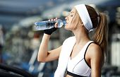foto of treadmill  - Smiling athletic woman drinking water on a treadmill - JPG