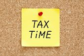 foto of irs  - Tax Time written on yellow sticky note pinned with red push pin on cork board - JPG