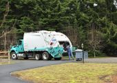 stock photo of trash truck  - A Sanitation Worker dumps a trash can into a garbage truck - JPG