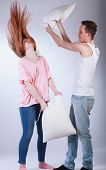 stock photo of pillow-fight  - Young couple having pillow fight on isolated grey background - JPG
