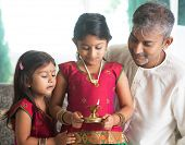 stock photo of diwali lamp  - Indian family in traditional sari celebrate diwali or deepavali at home - JPG