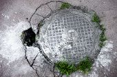 picture of manhole  - Manhole in cracked asphalt surface with a big hole near the cover - JPG