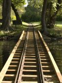 pic of train track  - A straight wooden train track disappearing into the forest on Toronto Island in Ontario Canada - JPG