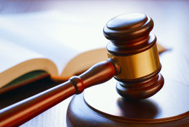 stock photo of punish  - brown gavel and open book on a wooden table of the law in the courtroom - JPG