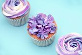 image of buffet  - Delicious sweet buffet with magenta cupcakes on cyan background - JPG