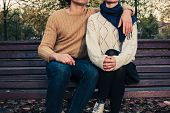 picture of youg  - A youg couple is sitting and holding each other on a park bench in autumn - JPG