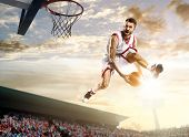 pic of slam  - Basketball player in action on background of sky and crowd - JPG