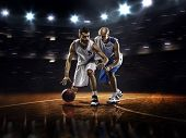 pic of basketball  - Two basketball players in action in gym in lights - JPG