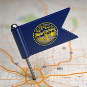 stock photo of nebraska  - Small Flag of Nebraska on a Map Background with Selective Focus - JPG