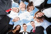 picture of huddle  - Directly below portrait of multiethnic businesspeople forming huddle against sky - JPG