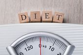image of indications  - Closeup of weight scale indicating Diet wooden blocks - JPG
