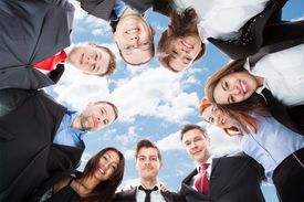 foto of huddle  - Directly below portrait of multiethnic businesspeople forming huddle against sky - JPG
