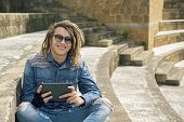 foto of dreadlocks  - freelancer guy with dreadlocks sitting on staircase with digital tablet typing message warm filter applied - JPG