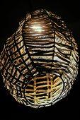 foto of lamp shade  - original wicker lampshade with lamp in the dark - JPG