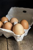 picture of low-light  - Fresh eggs in egg box in moody natural lighting vintage style set up - JPG