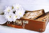 image of old suitcase  - Old wooden suitcase with old books and flowers on wooden background - JPG