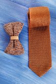 stock photo of tied  - Male tie and bow tie on color wooden table background - JPG