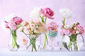 foto of vase flowers  - Beautiful spring flowers in glass vases on light pink background - JPG