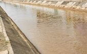 picture of rainy season  - image of brown water with cement canal in rainy season - JPG