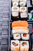picture of lunch box  - a sushi box or bento box with assorted sushi pieces over a dark black lunch mat - JPG