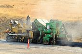 stock photo of paving  - Asphalt paving machine laying down a fresh layer of paving on a new road interchange project