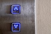 picture of elevators  - Elevator buttons glowing in neon blue up and down - JPG