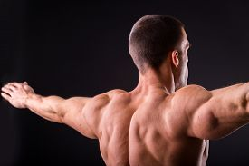 stock photo of bodybuilder  - Muscular man bodybuilder. Man posing on a black background, shows his muscles. Bodybuilding, posing, black background, muscles - the concept of bodybuilding. Article about bodybuilding. ** Note: Shallow depth of field - JPG