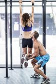 stock photo of pull up  - Trainer lifting a muscular woman doing pull up exercises - JPG