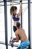 picture of pull up  - Trainer lifting a muscular woman doing pull up exercises - JPG