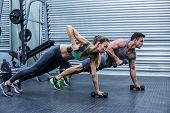 Muscular couple doing plank exercise while lifting weights poster
