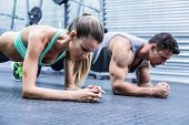 stock photo of day care center  - Side view of a muscular couple doing planking exercises - JPG