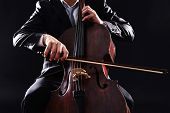 image of cello  - Man playing on cello on dark background - JPG