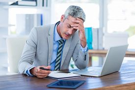 foto of irritated  - Irritated businessman trying to work in office - JPG