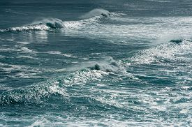 image of horsetail  - Two backlit lines of breaking waves with horsetails of spray in a dark aquamarine sea with cover of white foam - JPG