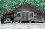 picture of log cabin  - An old log cabin with an attached one car garage and a dilapidated old truck sitting in it - JPG