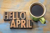 Hello April word abstract in vintage letterpress wood type with a cup of coffee poster