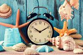 an alarm clock being adjusted forward one hour at the beginning of the summer time, many conches and poster