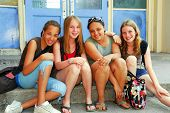 stock photo of young girls  - Portrait of a group of young smiling school girls sitting on steps near school building - JPG