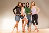 Picture of four girls standing on the wood floor with bare feets. Photo is a part of small sequented serie.