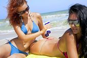 picture of nudist beach  - Beautiful woman smearing with sunscreen her girlfriend on the beach - JPG