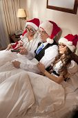 image of promiscuous  - Manager with two his subordinates watching tv on New Year - JPG