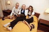 foto of promiscuous  - Manager with two his subordinates reading a business plan sitting in bed on New Year - JPG