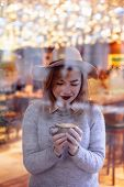 The Lovely Girl In Cafe Behind A Window. The Girl Holding A Hot Drink And Looking At The Cup. Bright poster