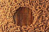 Top View Of The Whole Fusilli Pasta, On A Wooden Background. Free Space For Text poster