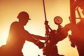 Oil Worker Is Checking The Oil Pump On The Sunset Background. poster