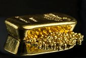 Gold Bar And A Pile Of Pure Gold Granules On A Mirror Dark Background. Selective Focus. poster