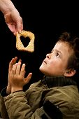 picture of humble  - Feeding the poor concept with dirty kid receiving slice of bread  - JPG