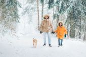 Father And Son Dressed In Warm Hooded Casual Parka Jacket Outerwear Walking In Snowy Forest With His poster