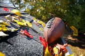 Rain gutter full of autumn leaves with a football